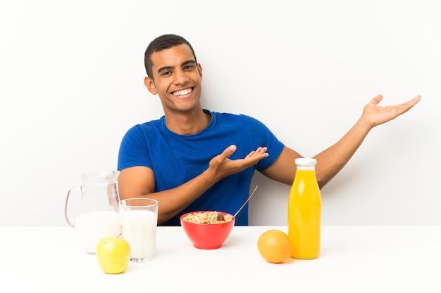 Молодой человек завтракает в таблице, протягивая руки в сторону за приглашение прийти