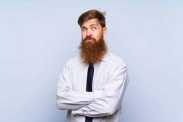 アイデアを考えて孤立した壁の上の長いひげを持ったビジネスマン