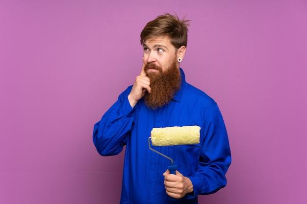 アイデアを考えて孤立した紫色の壁の上の長いひげを持つ画家男