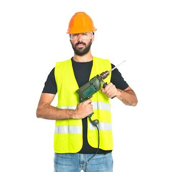 白い背景のドリルを持つ労働者