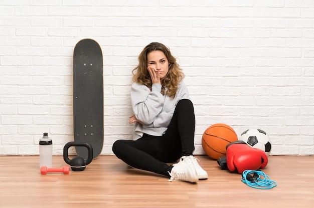 不幸で不満の床に座っている若いスポーツ女性