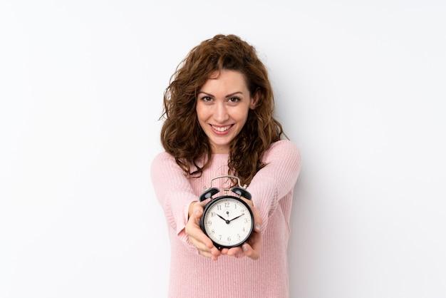 ビンテージ目覚まし時計を保持している若いきれいな女性