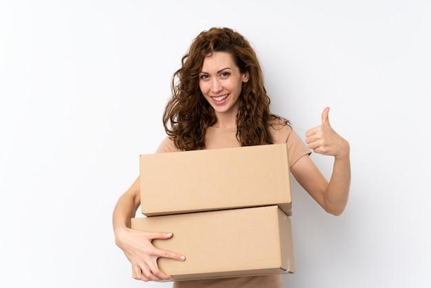 箱を抱えて親指で別のサイトに移動する若いきれいな女性