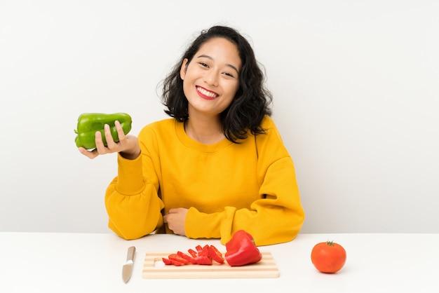 テーブルで野菜と若いアジアの女の子