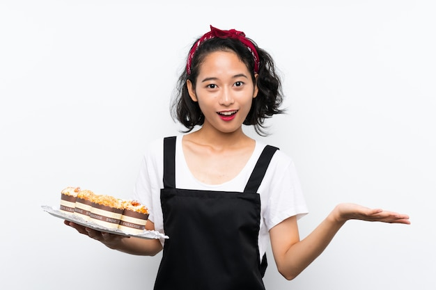 ショックを受けた表情で孤立した白い背景の上にマフィンケーキの多くを保持している若いアジアの女の子