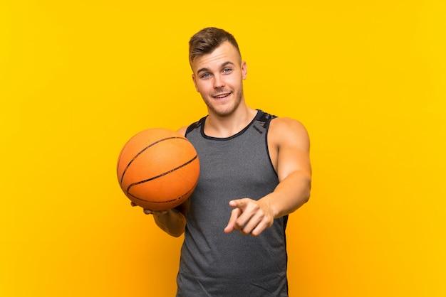 孤立した黄色の背景にバスケットボールを保持している若いハンサムな金髪男は自信を持って表現であなたに指を指す
