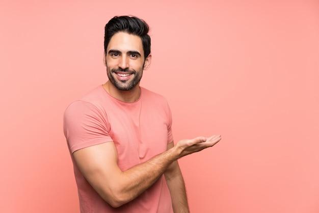 来て招待する側に手を拡張する分離のピンクの背景の上のハンサムな若い男