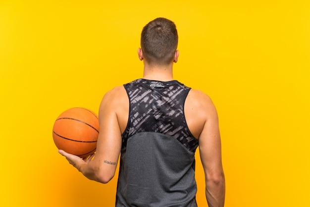 バックポジションで孤立した黄色の背景上にバスケットボールを置く若いハンサムな金髪男