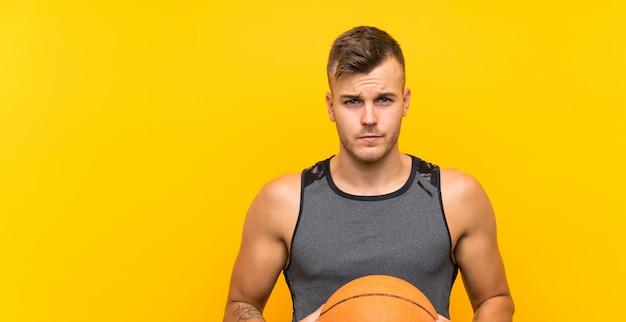 孤立した黄色の背景にバスケットボールを保持している若いハンサムな金髪男
