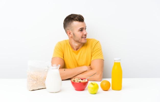 Молодой блондин человек завтракает смех