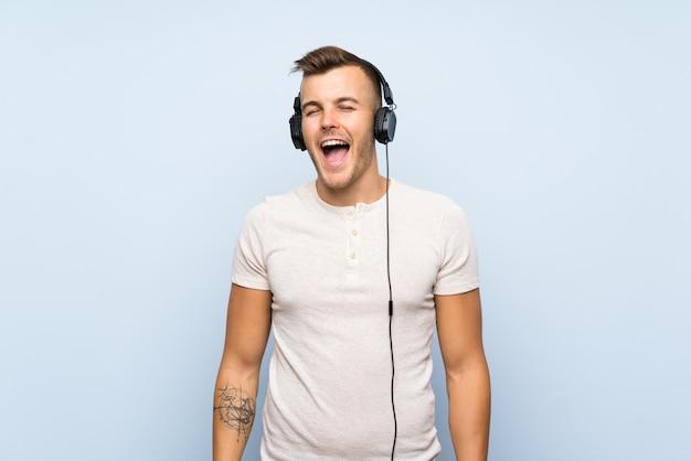 Молодой красивый белокурый человек над изолированной голубой предпосылкой слушая к музыке с наушниками