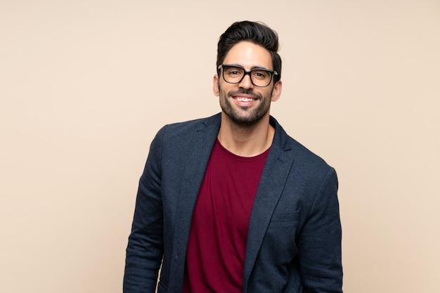 Красивый молодой человек на изолированном фоне с очками и счастливым