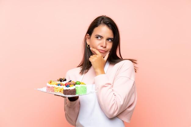 アイデアを考えてさまざまなミニケーキの多くを保持している若い女の子