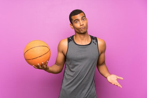 肩を持ち上げながら疑わしいジェスチャーを作るバスケットボールのボールを持つ若いスポーツ男