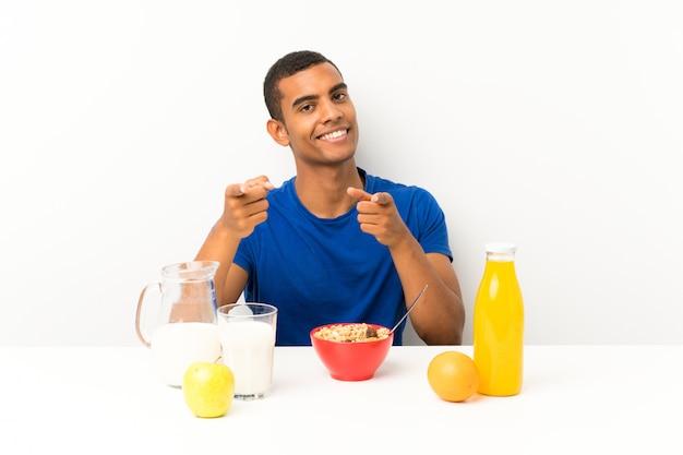 Молодой человек завтракает в таблице указывая