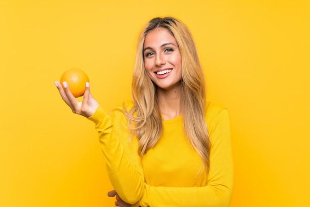 黄色の壁にオレンジをかざす若いブロンドの女性