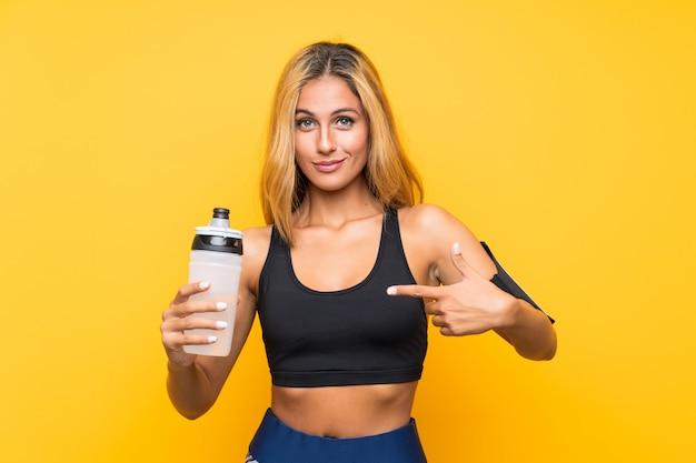 孤立した壁の上の水のボトルを持つ若いスポーツ女性