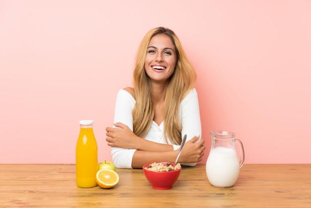 Молодая белокурая женщина имея смеяться над молока завтрака