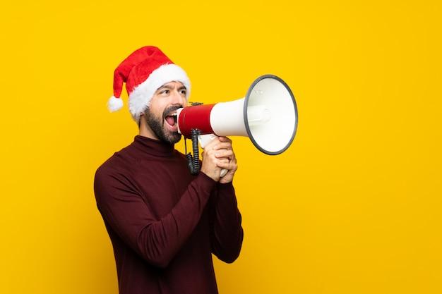 メガホンを通して叫んで孤立した黄色の壁の上のクリスマス帽子の男