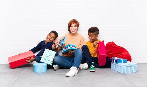 クリスマス休暇のための多くの贈り物の中で母親と一緒にアフリカ系アメリカ人の子供たち