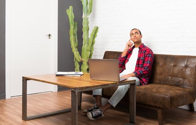 深刻な顔を見上げてリビングルームでラップトップを持つアフリカ系アメリカ人
