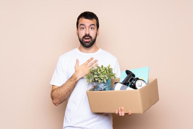 箱を持って、右を見ながら驚いてショックを受けた新しい家に移動する男