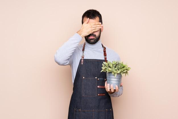 手で目を覆っている植物を抱きかかえた、何かを見たくない