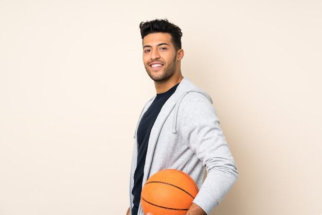 バスケットボールのボールで孤立した背景の上の若いハンサムな男