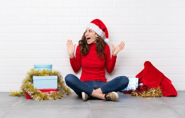 驚きの表情で床に座ってクリスマス休暇の女の子