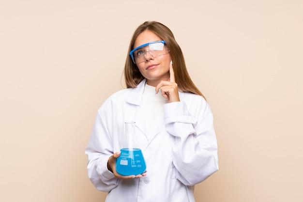 Молодая белокурая женщина над изолированной предпосылкой с научной пробиркой