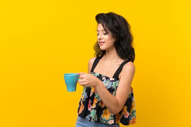 Молодая женщина на желтом фоне держит чашку горячего кофе