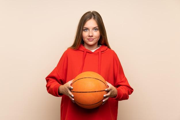 バスケットボールのボールで孤立した背景の上の若いブロンドの女性