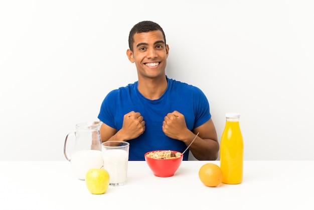 Молодой человек завтракает в таблице празднует победу