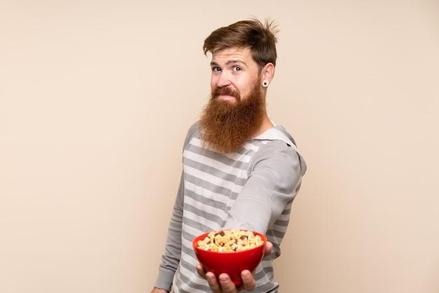 Рыжий мужчина с длинной бородой держит миску каши