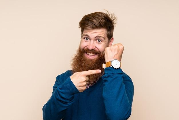 手の時計を示す長いひげと赤毛の男