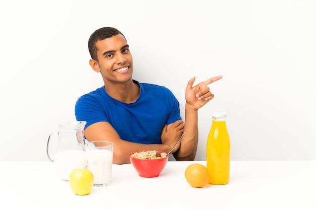 Молодой человек завтракает в таблице, указывая пальцем в сторону