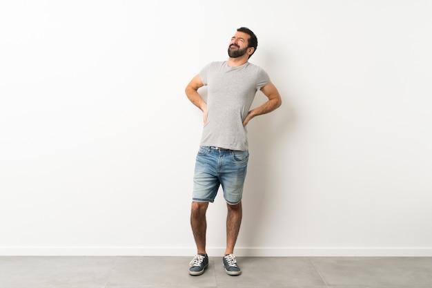 Полнометражный снимок красавца с бородой, страдающего от боли в спине