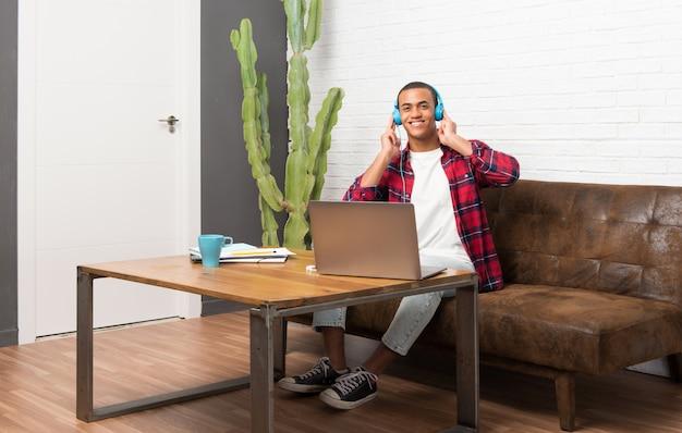 ヘッドフォンで音楽を聴くリビングルームでラップトップを持つアフリカ系アメリカ人