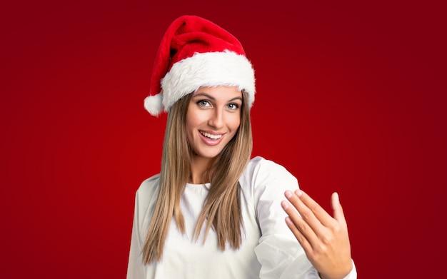 来て招待して孤立した壁の上のクリスマス帽子の少女