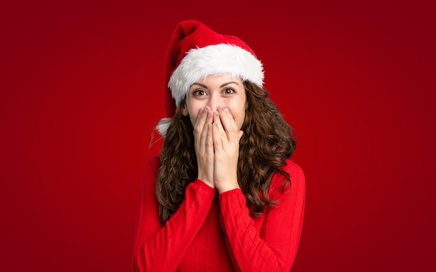 Девушка с шляпой рождества над изолированной желтой стеной с выражением лица сюрприза
