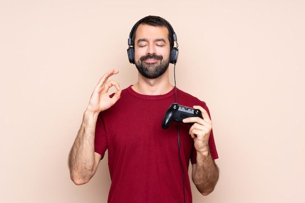 Человек играет с контроллером видеоигры над изолированной стеной в позе дзен