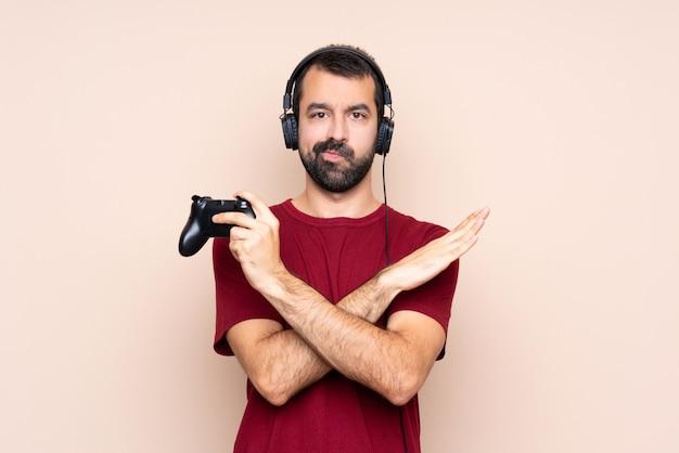 Человек играет с контроллером видеоигры над изолированной стеной, не делая жест
