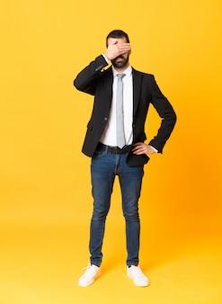 手で目を覆っている孤立した黄色の背景の上のビジネスの男性の全身ショット、何かを見たくない