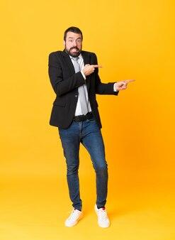 Полнометражный снимок делового человека на изолированном желтом фоне испуганный и указывая на сторону