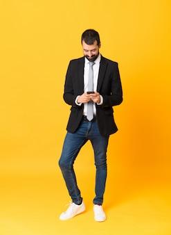 携帯電話でメッセージを送信する孤立した黄色の背景の上のビジネスの男性の全身ショット