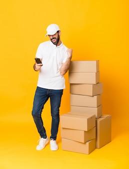 勝利の位置に電話で分離された黄色の背景上のボックスの中で配達人の全身ショット