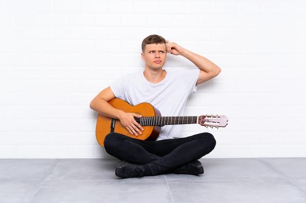 疑問を持つギターと混乱の表情を持つ若いハンサムな男