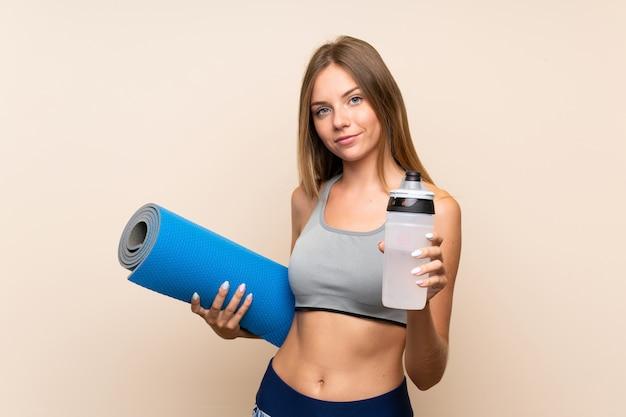 Молодая белокурая девушка спорта над изолированной предпосылкой с бутылкой с водой спорт и с циновкой