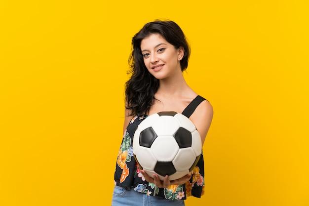Молодая женщина над изолированной желтой предпосылкой держа футбольный мяч