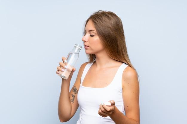 Молодая блондинка с бутылкой воды на изолированном фоне
